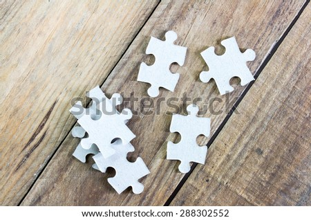 Puzzle on wooden background. - stock photo