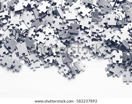 Puzzle pieces on a white wooden surface closeup. Black and white image