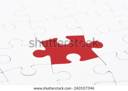 Puzzle pieces, one piece with red color texture. Conceptual image of connection, solution and business strategy. - stock photo
