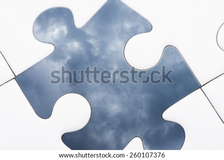 Puzzle pieces, one piece with  texture of dark sky and storm clouds. Conceptual image of connection, challenge and business strategy. - stock photo