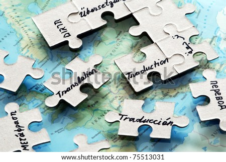 puzzle pieces placed on world map ,reffering to different languages and translations - stock photo