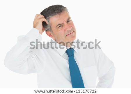 Puzzled businessman scratching his head - stock photo