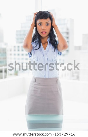 Puzzled businesswoman holding her head in office - stock photo