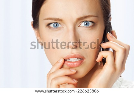Puzzled businesswoman with cellphone, at office - stock photo
