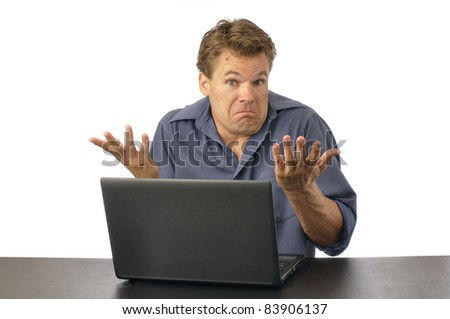Puzzled man at computer shrugs shoulders and expresses lack of knowledge - stock photo