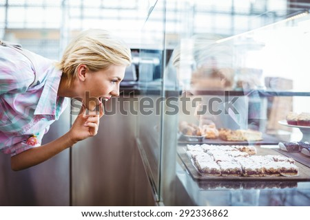 Puzzled pretty woman looking at cup cakes at the bakery - stock photo