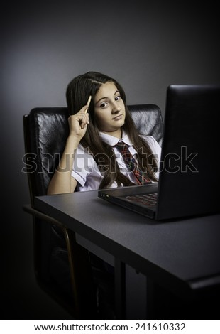 Puzzled schoolgirl sitting at desk with laptop in front and pencil in hand, looking at the camera. - stock photo