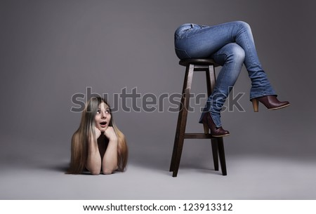 puzzled young woman looking her own legs separated from her body on grey background - stock photo
