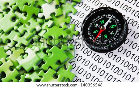 puzzles and compass on a binary code - stock photo