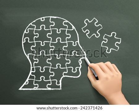 puzzles in head shape drawn by hand over chalkboard  - stock photo