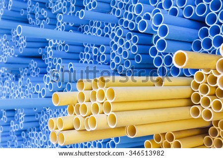 PVC pipes for electric conduit (yellow) and water (blue) - stock photo