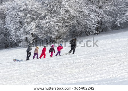 Pyatigorsk, Russia - January 02, 2016: Children in colorful costumes with sled together with their parents flow along white snow.