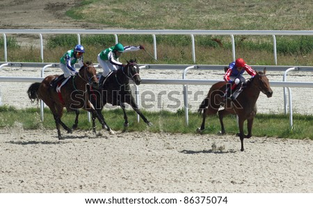 PYATIGORSK,RUSSIA - JULY 12: Jockeys (L - R)Sergei Lavrikov, Sergei Gurciev and Hamzat Ulubaev race for the prize of Pyatigorsk on July 12, 2009 in Pyatigorsk, Caucasus, Russia.