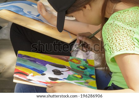 PYATIGORSK, RUSSIA - JUNE 1, 2014: Children's Day. The young artist behind work
