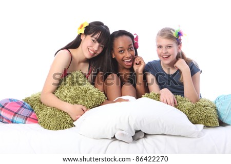 Pyjama party fun for three teenage girl friends, a mixed race african american, oriental Japanese and blonde caucasian school mates all wearing flower or feather hair accessories. - stock photo