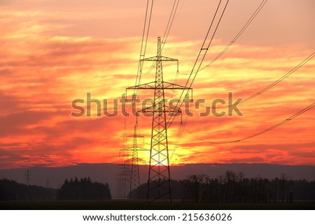 Pylon and power lines at sunset with red sky and sun - stock photo