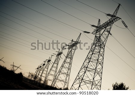 Pylon and transmission power line in sunset - stock photo