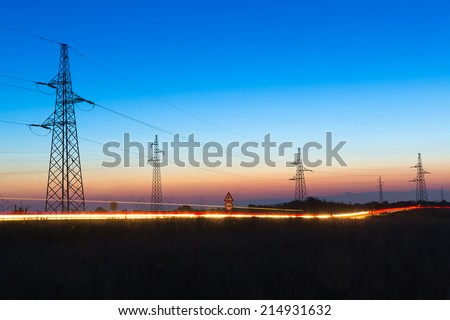Pylons and electrical power lines at dusk with traffic lights in front - stock photo