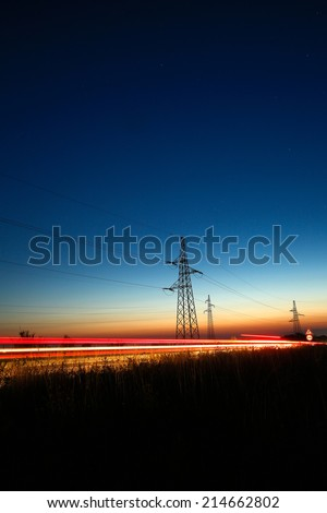 Pylons and electricity powerlines at night with traffic lights in front - stock photo
