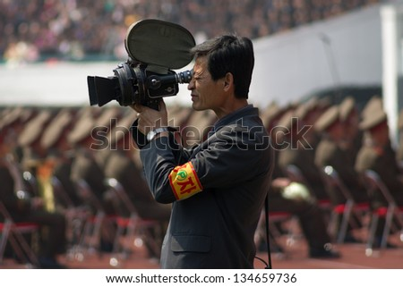 PYONGYANG, NORTH KOREA - CIRCA APRIL 2012: North Korea cameramen with old camera at the military parade celebrating centenary birth of President Kim Il Sung in Pyongyang circa April 2012. - stock photo
