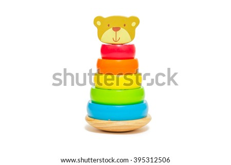 Pyramid build from colored wooden rings with a bear head on top. Toy for babies and toddlers to joyfully learn mechanical skills and colors. Studio shot on white background. - stock photo