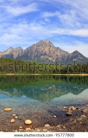 Pyramid mountain and lake with reflection on the smooth water. Jasper National Park, Alberta, Canada - stock photo