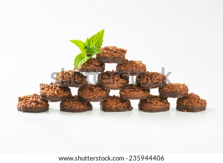 pyramid of chocolate chip cookies decorated with leaves of herb - stock photo