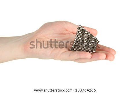Pyramid of metal balls for neocube (toy) on man hand, isolated on white