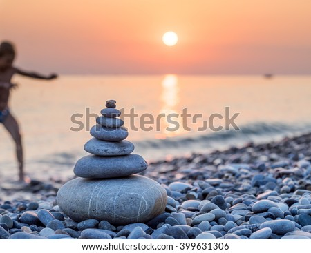 Pyramid of stones for meditation lying on sea coast at sunset. Blurred silhouette of a child, coming out of the sea to the shore