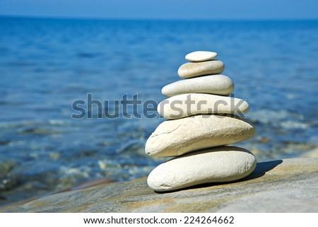 Pyramid of stones zen balance in sea shore on sunny day - stock photo
