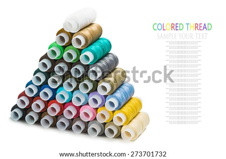 Pyramid of the Sewing multi colored thread isolated on white. Text for example, and can be easily removed - stock photo