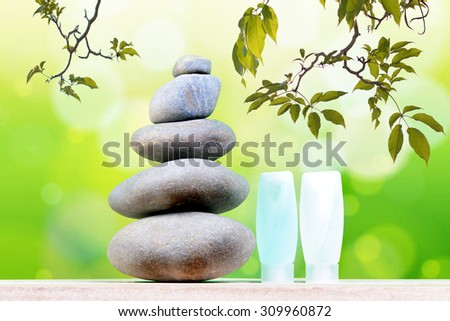 Pyramid of the stones isolated and tree branches with green leaf or Zen pebbles balance on green bokeh background. Spa Concept. - stock photo