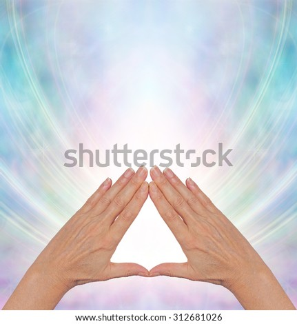 Pyramid Power Energy Healing - female hands making a triangle shape on a misty blue flowing triangular shaped energy field with plenty of copy space above - stock photo