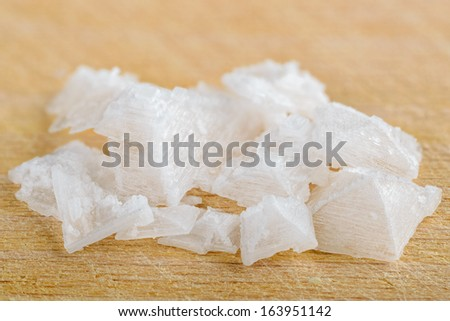 Pyramid shaped salt flake crystals on cutting board. - stock photo