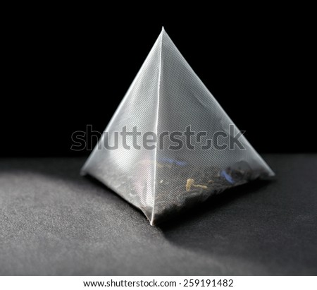 pyramid tea bag on black background - stock photo