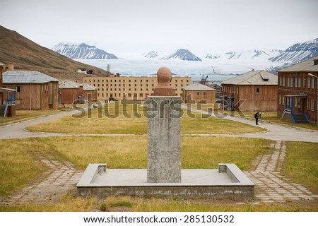PYRAMIDEN, NORWAY - SEPTEMBER 03, 2011: View to abandoned Russian arctic settlement Pyramiden with the bust of Lenin in the foreground in Pyramiden, Norway. - stock photo