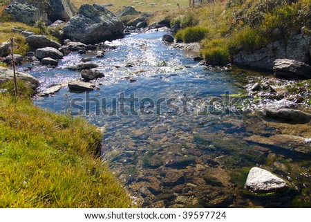 Pyrenees mountain, autumn day, sunlight in water, small brook.