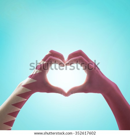 Qatar flag pattern on people hands in heart shape on vintage blue sky background, symbolic sign language expressing love, unity, harmony of people in country/ nation concept: Happy National day  - stock photo