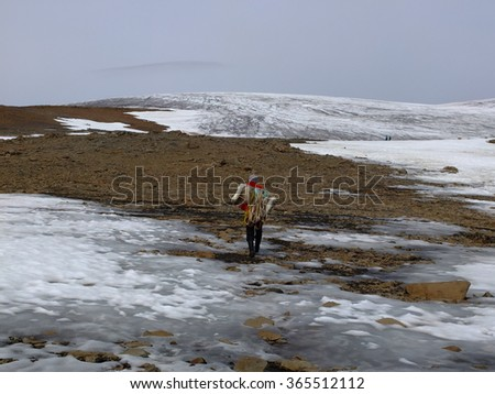 QEQERTARSUAQ, GREENLAND, JULY 25, 2015 Dog sledge driver going to the dogs on the glacier