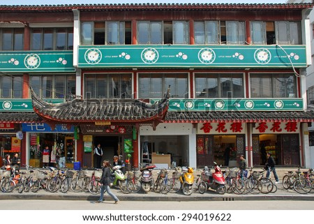 QIBAO, SHANGHAI-MARCH 16, 2010: bicycle parking , shops and restaurant at the village main entry. Qibao water village is Shanghai tourist attraction with 1000000 visitors year. - stock photo