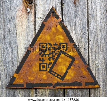 QR Code with Smartphone Icon on Weathered Triangular Yellow Warning Sign. Grange Background. - stock photo