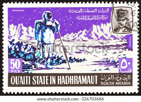 """QU'AITI STATE IN THE HADHRAMAUT - CIRCA 1967: A stamp printed in Yemen from the """"Apollo moon project """" issue shows Astronaut taking measurements on the moon, circa 1967.  - stock photo"""