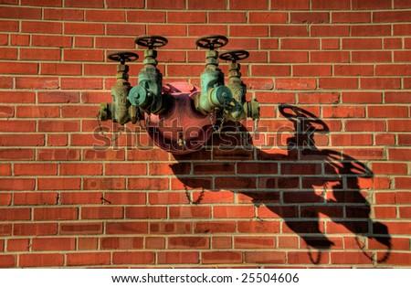 Quad Fire Plug on Brick wall with shadow - stock photo