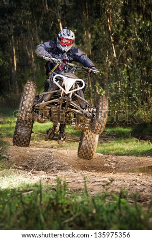 Quad rider jumping on a forest trail. - stock photo