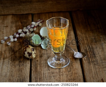 quail eggs in a glass, salt and twigs of willow on a wooden background - stock photo