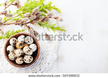 Quail eggs in a wooden bowl Easter white background Willow and green spring branch with leaves Top view Copy space