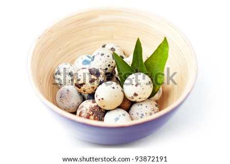 Quail eggs in bowl with leaves. With clipping path. - stock photo