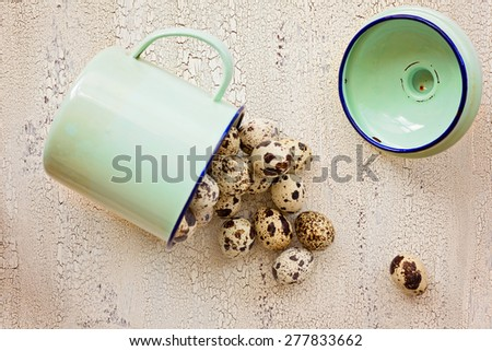 Quail eggs in green metal cup, ?n light color wooden background, top view - stock photo