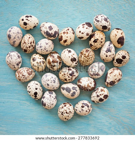 Quail eggs in shape of heart on a blue wooden background, top view, square frame - stock photo