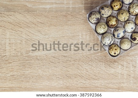 Quail eggs in the tray on a wooden background and empty space for text. Top view with copy space